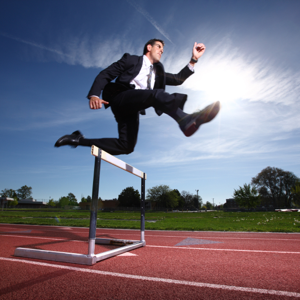 Businessman hurdling on a running track