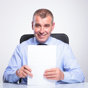A senior businessman sitting at his desk and holding some documents