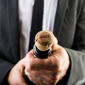 Close up of businessman opening bottle of champagne with 2015 on the cork