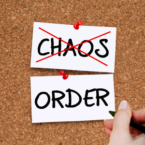 CHAOS crossed out in red and a woman writing ORDER on a cork noticeboard