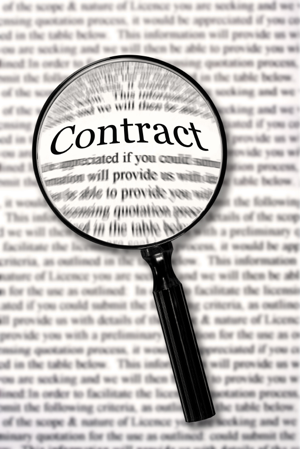 Magnifying glass over contract document, highlighting the word Contract
