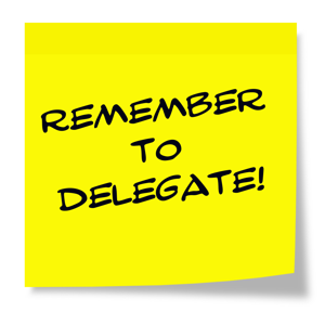 Remember to delegate written on a yellow sticky note