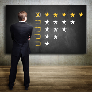 Businessman looking at a five star rating on a blackboard