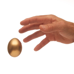 Man's hand reaching for a golden egg