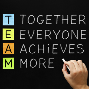 Hand writing TEAM - Together Everyone Achieves More with white chalk on a blackboard