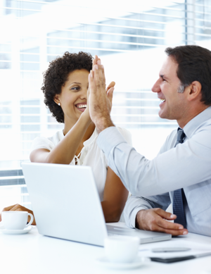 Business people high-fiving in the office