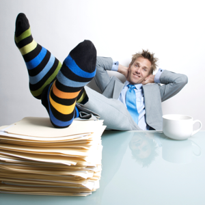Project manager relaxing with his feet up on a pile of folders