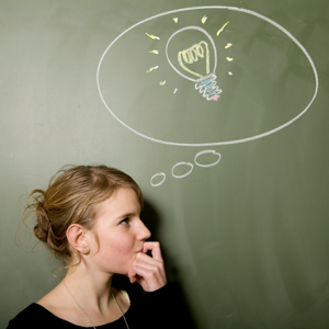 Woman thinking with a light bulb drawn on a blackboard