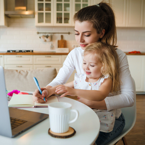 Businesswoman wrting in a notbook, with a child on her knee sitting at the kitchen table with a computer and mug