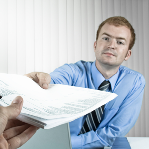 Manager passing a document to a colleague