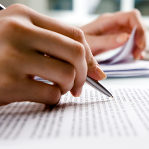 A close up of a hand holding a pen while reviewing a document