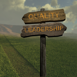 Wooden sign in a field reading quality and leadership
