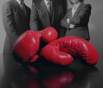 Close-up of red boxing gloves and business people
