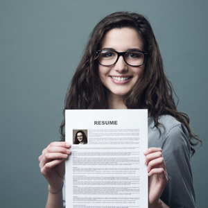 Young smiling and cheerful woman holding up her resume