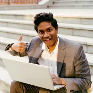Young Indian man in a white shirt and a business suit sitting on some steps with a laptop, smiling and typing