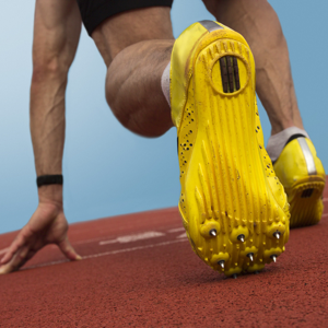 Close up of sprinters yellow spikes on a running track