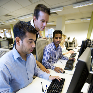 A team of people working together in a computer lab