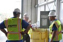 Three construction workers standing by a waste bin