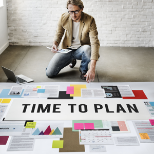 Man knealing in front of a large project plan on the floor