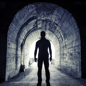 Young man standing in a dark tunnel