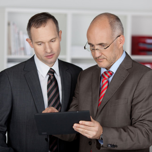 Two serious businessmen working with a tablet computer